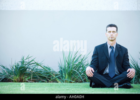 Businessman sitting on ground outdoors, meditating, eyes closed - Stock Photo