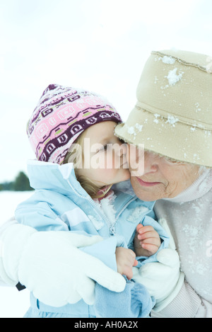 Toddler girl kissing grandmother on cheek in snow, close-up - Stock Photo