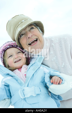 Senior woman embracing granddaughter in snow, both smiling, waist up - Stock Photo
