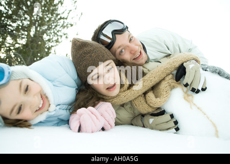 Three young friends reclining in snow, piled up, one smiling at camera - Stock Photo