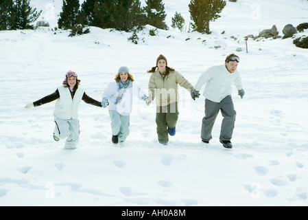 Four young friends running together in snow, holding hands, full length - Stock Photo