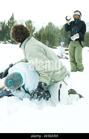 Young friends having snowball fight in snow - Stock Photo