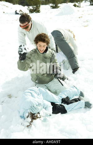 Young friends having snowball fight, one lying on ground, covering head with arms - Stock Photo