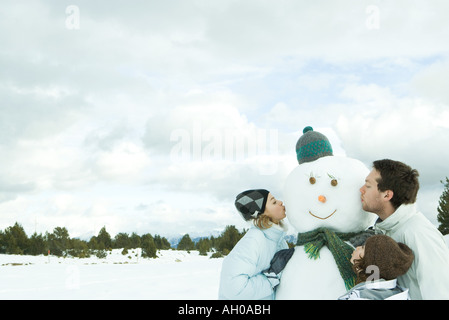Three young friends kissing snowman, head and shoulders - Stock Photo