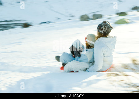 Young friends sledding down hill together, blurred motion - Stock Photo