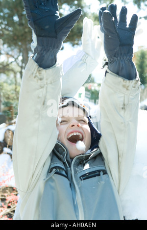 Boy with arms raised in snow, smiling, eyes closed, head and shoulders - Stock Photo