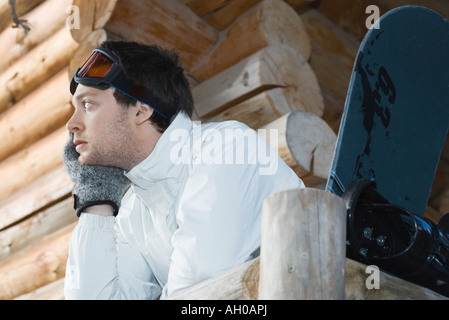 Young man in ski gear standing against deck of log cabin, leaning on rail - Stock Photo