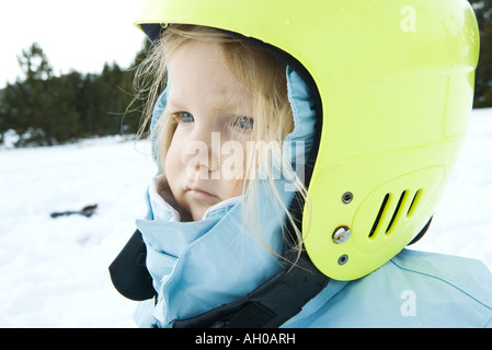 Toddler girl wearing winter coat and helmet, in snowy landscape, portrait - Stock Photo
