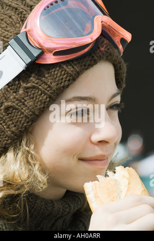 Girl wearing ski gear, eating sandwich, close-up - Stock Photo