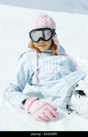 Preteen girl wearing ski gear, reclining in snow, portrait - Stock Photo