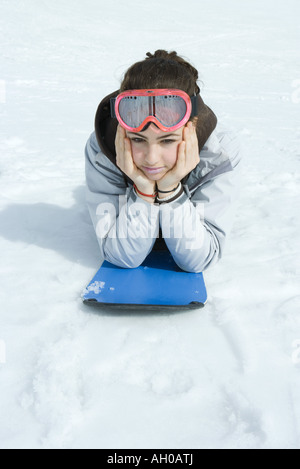 Preteen girl lying on snowboard in snow, portrait - Stock Photo