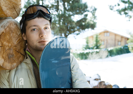 Young man with snowboard, portrait - Stock Photo