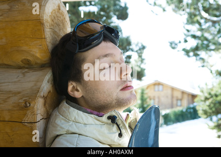 Young man leaning against log cabin, with snowboard, eyes closed - Stock Photo