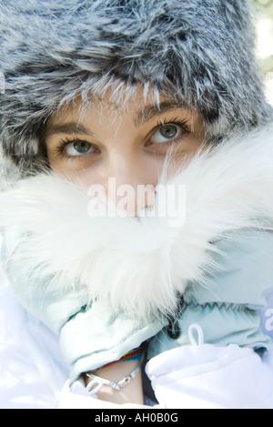 Teenage girl wearing fur hat, pushing fur collar over mouth, close-up portrait - Stock Photo