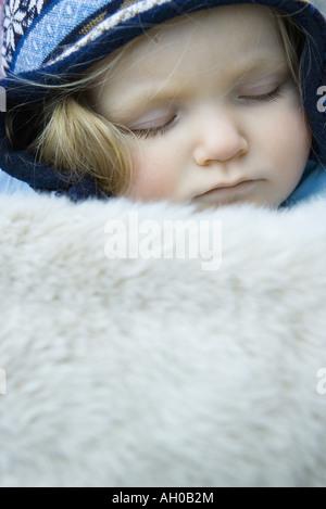 Toddler girl, sleeping under fur blanket, portrait - Stock Photo