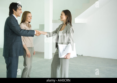 Real estate agent shaking hands with young couple in empty home interior