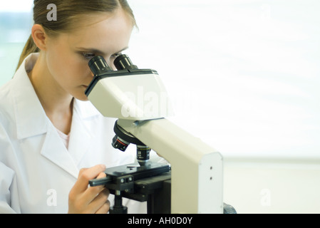 Young woman using microscope - Stock Photo