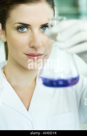 Young researcher holding up conical flask - Stock Photo