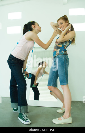 Two young friends standing together, one leaning to apply lipstick to the other, one looking at camera - Stock Photo