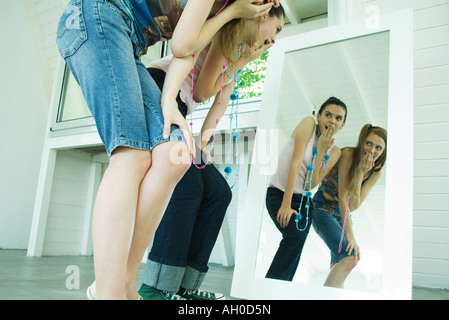 Two young friends bending over, looking at selves in mirror, covering mouths - Stock Photo