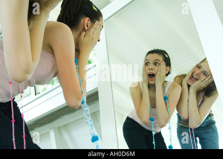 Two young friends bending over, looking at selves in mirror, hands on faces - Stock Photo