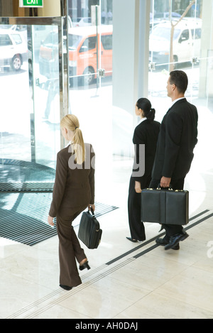 Business associates with briefcases exiting office lobby - Stock Photo