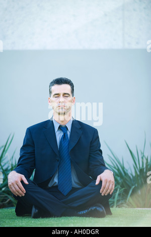 Businessman sitting cross-legged on grass, eyes closed - Stock Photo