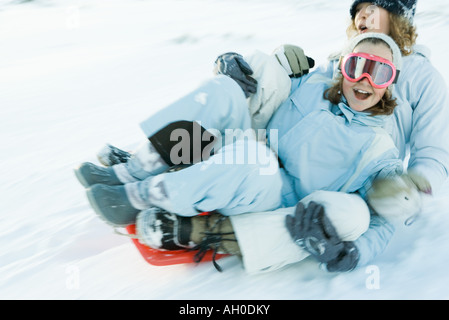 Two young friends riding sled together, blurred motion - Stock Photo