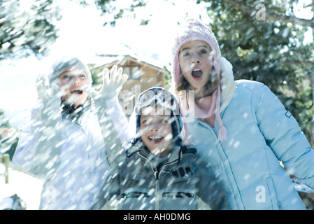 Young friends standing in falling snow, smiling, waist up - Stock Photo