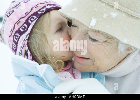 Toddler girl kissing grandmother on cheek, both dressed in winter clothing, close-up - Stock Photo