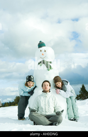 Young man meditating in front of snowman, two sisters crouching behind, smiling at camera - Stock Photo