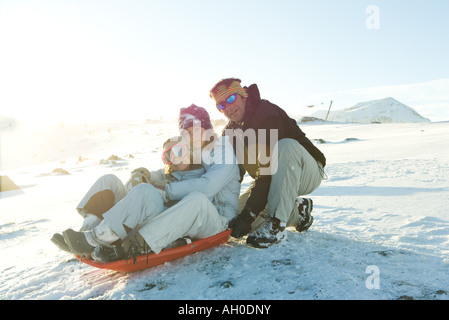 Mature man crouching behind sled with two daughters, smiling at camera - Stock Photo