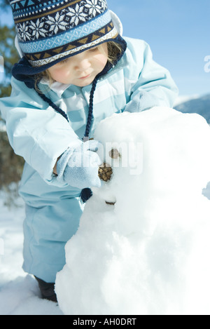 Toddler girl building snowman, dressed in winter clothing - Stock Photo