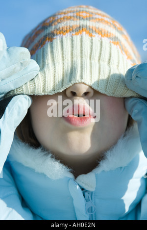 Girl pulling knit hat down over eyes, puckering, close-up - Stock Photo