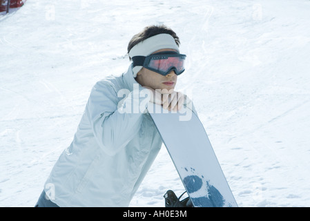 Young man leaning on snowboard - Stock Photo