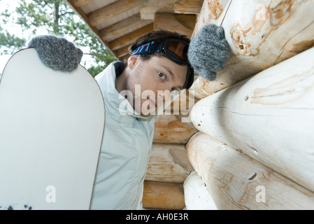 Young man with snowboard, leaning on wall of log cabin, looking at camera - Stock Photo