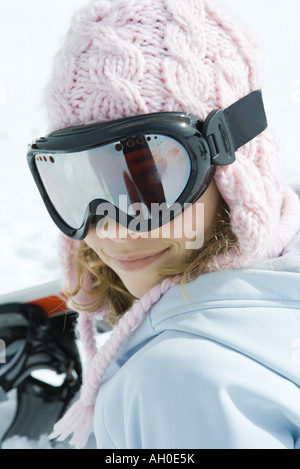 Preteen girl wearing ski gear, smiling at camera, portrait - Stock Photo