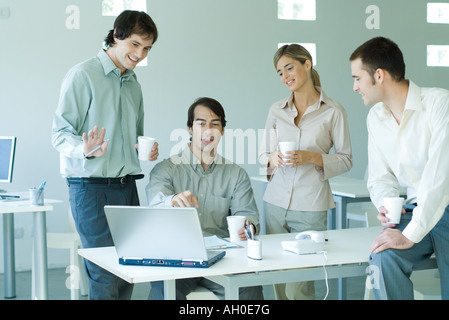 Four business associates in office, looking at laptop computer, holding coffee cups - Stock Photo