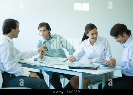 Business associates seated at table, chatting, three quarter length - Stock Photo