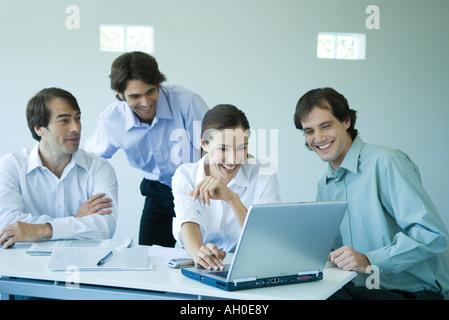Four business associates using laptop computer, smiling - Stock Photo