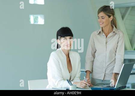 Two young businesswomen in office, smiling at camera - Stock Photo
