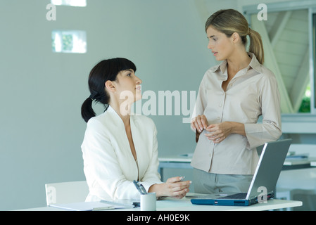 Two young businesswomen in office, looking at each other, discussing - Stock Photo