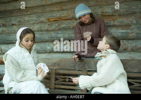 Young friends playing cards outdoors, dressed in winter clothing - Stock Photo