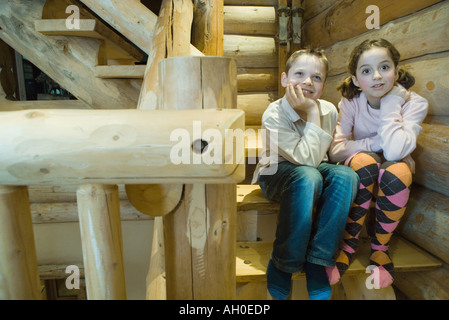 Boy and girl sitting side by side on steps, smiling, full length - Stock Photo