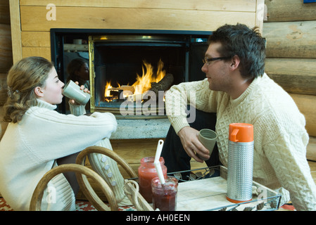 Young man and teenage girl sitting by fireplace, drinking hot beverages, looking at each other - Stock Photo
