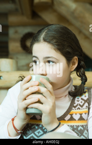 Teenage girl drinking hot beverage, looking away - Stock Photo