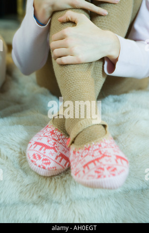Teenage girl hugging knees, wearing tights and slippers, cropped view of legs
