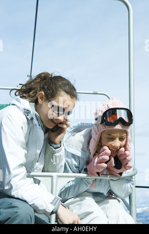 Young friends on chair lift, one using cell phone, both dressed in winter clothing - Stock Photo