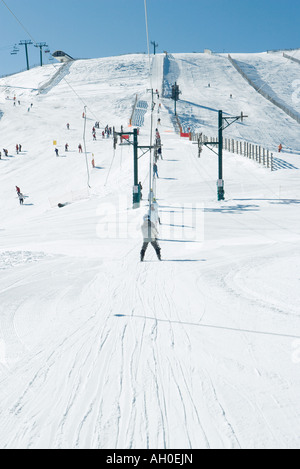 Young skiers using ski lift . in the distance, rear view - Stock Photo