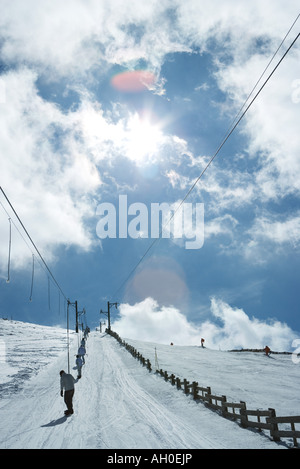 Young skiers using ski lift on hill. rear view, in the distance - Stock Photo
